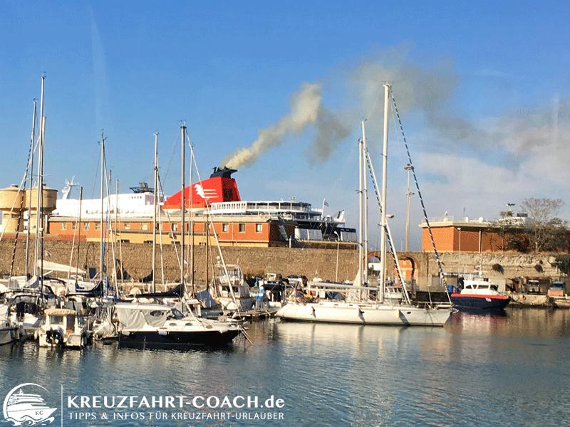 Starker Rauch aus Schiffsschornstein im Hafen.