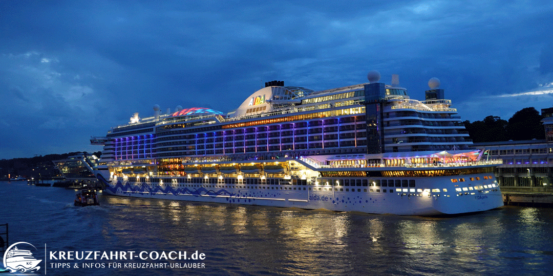 Blick vom Schiff auf die beleuchtete AIDAperla am Abend.