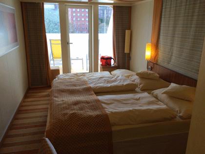 Blick über das Doppelbett zum Balkon.