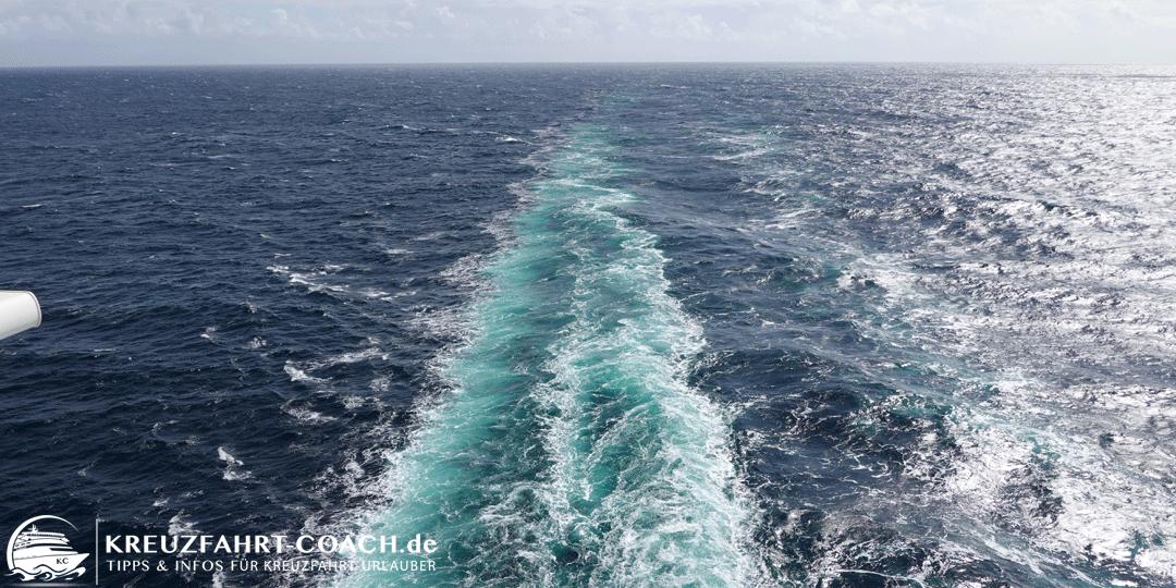 Blick vom Schiff nach Achtern auf die Heckwellen und den Horizont.