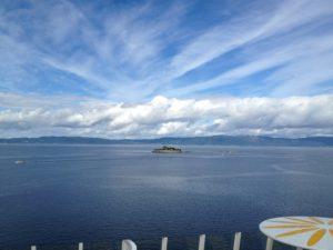 Meer, Insel vor Festland und Wolken