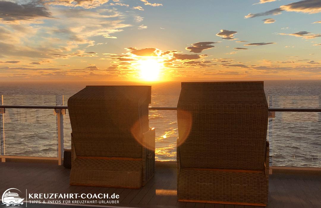 Blick über die Strandkörbe an Bord in den Sonnenuntergang.